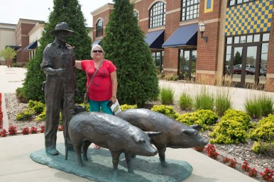 Judi by the farmer and pig sculpture outside