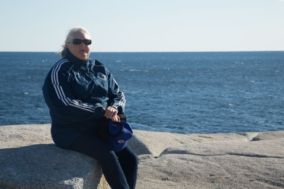 Peggys Cove with Judi sitting on the rocks below the light