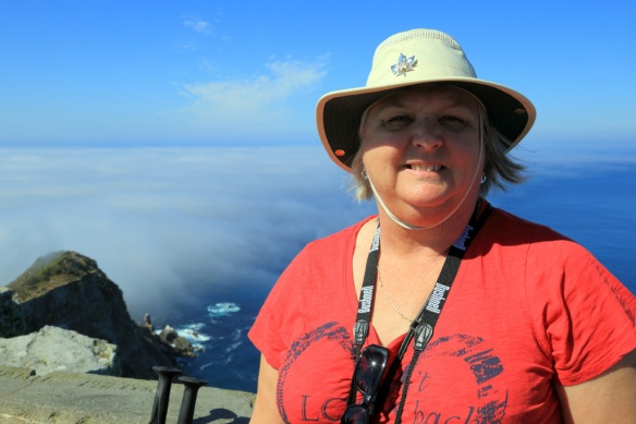 Judi at the lighthouse with the clearly defined fog line in background