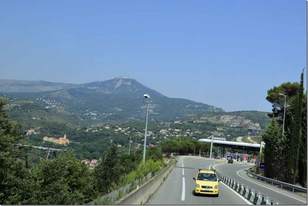 Returning to Cannes highway toll plaza and mountain behind Monaco well developed