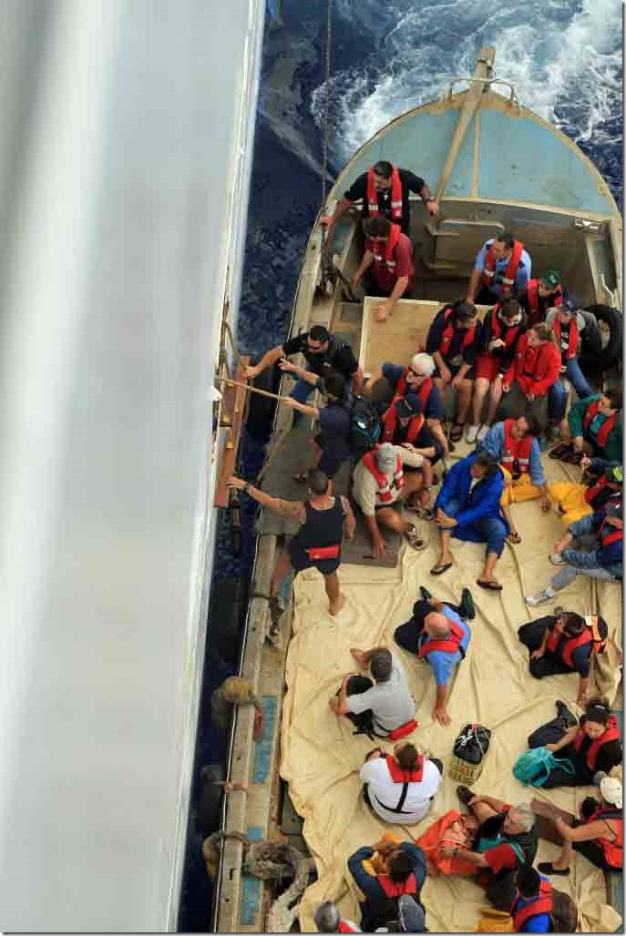 Long boat loaded with Pitcairn residents preparing to send first person aboard