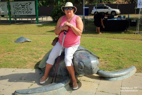 Judi sitting on turtle artwork